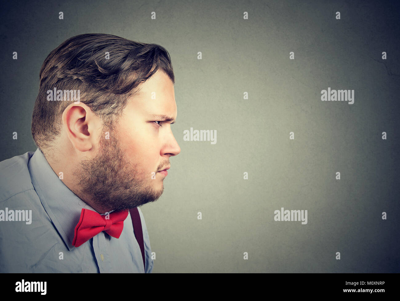 Chunky formal man looking away seriously with angry expression. - Stock Image