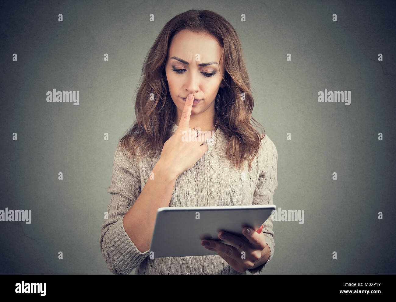 Young casual woman watching tablet and looking puzzled touching lips. - Stock Image