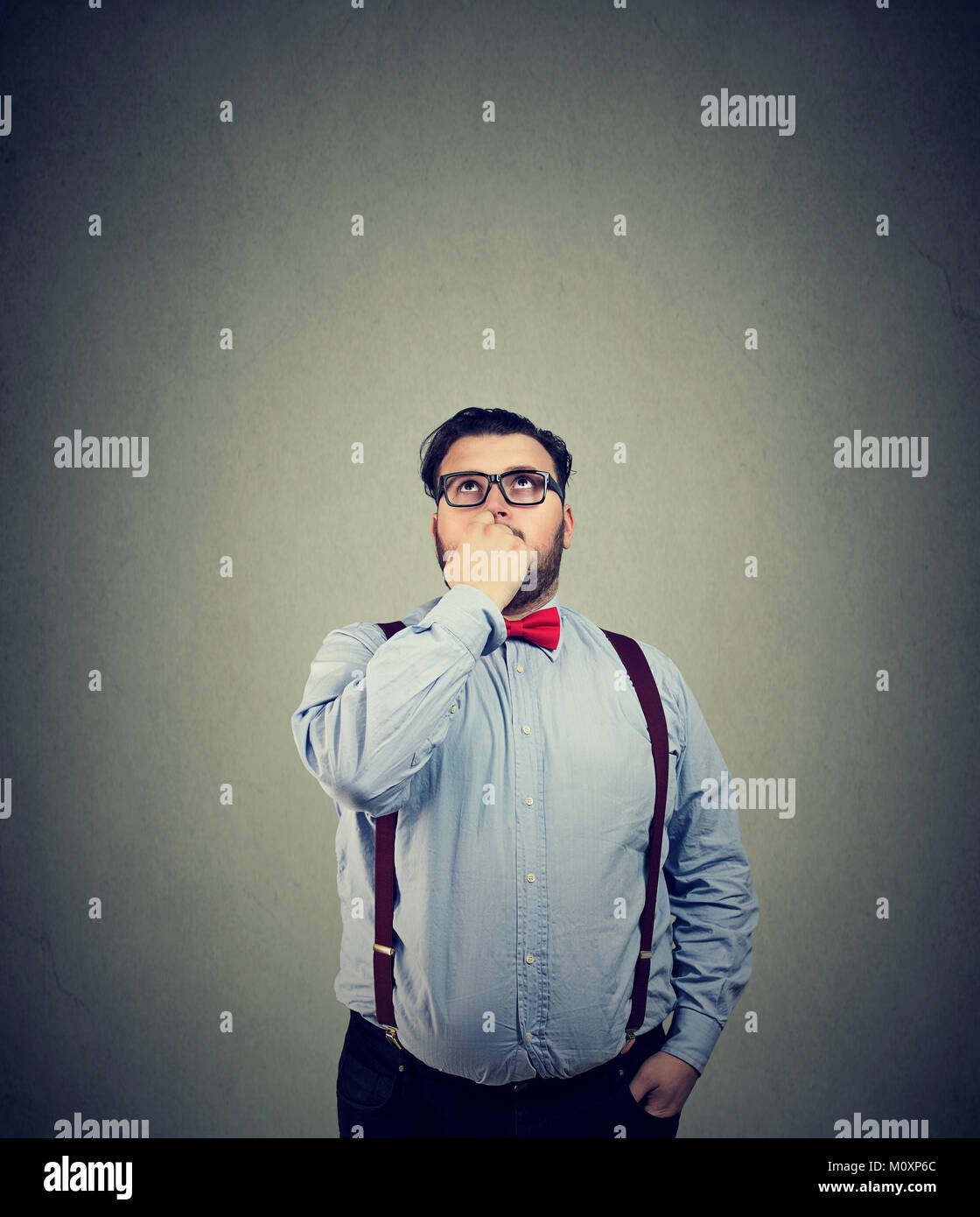 Young man in eyeglasses looking up and thinking thoroughly making important decision. - Stock Image