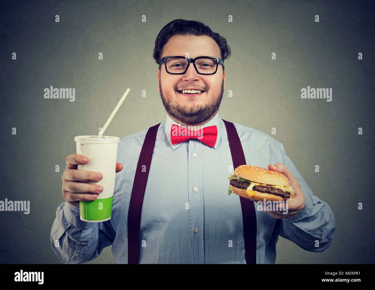 Young happy man looking excited while having burger and soda looking at camera. - Stock Image