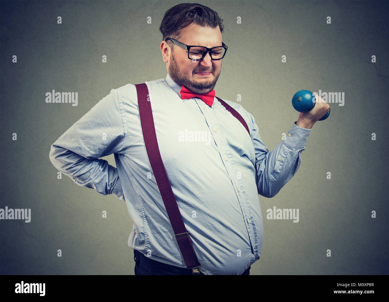 Young overweight man applying force to lift dumbbell frowning. - Stock Image