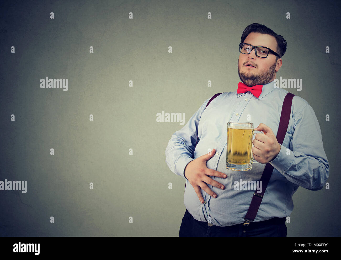 Young overweight man drunk with beer having potbelly. - Stock Image