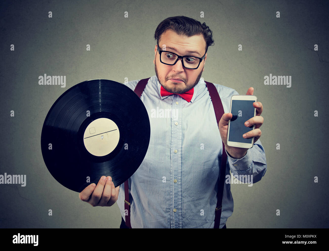Chunky man holding vinyl record and smartphone comparing old and new. - Stock Image