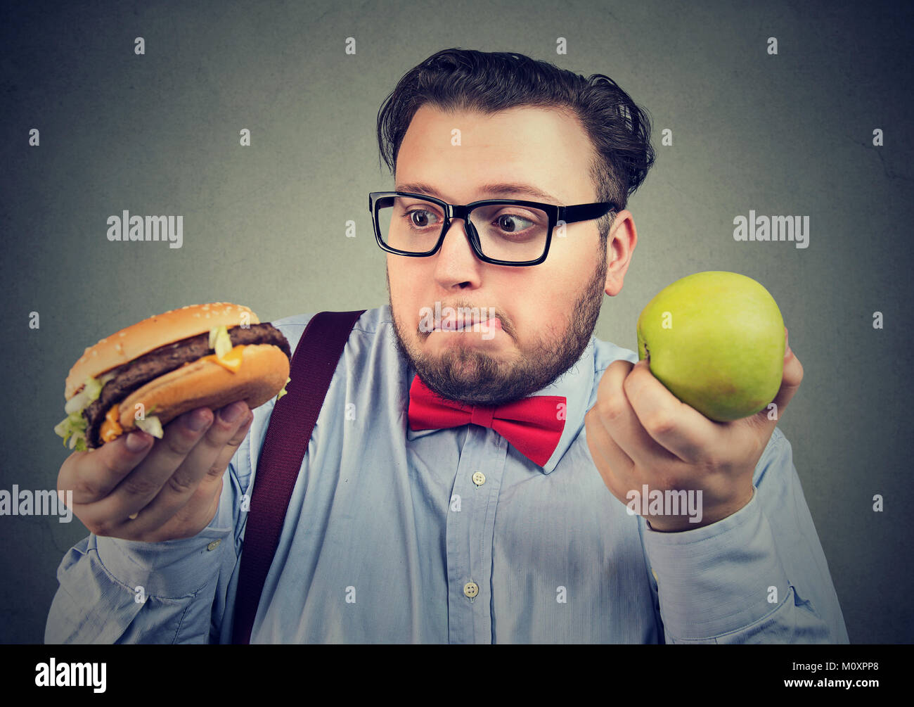 Chubby man in eyeglasses craving delicious burger instead of green apple looking confused. - Stock Image