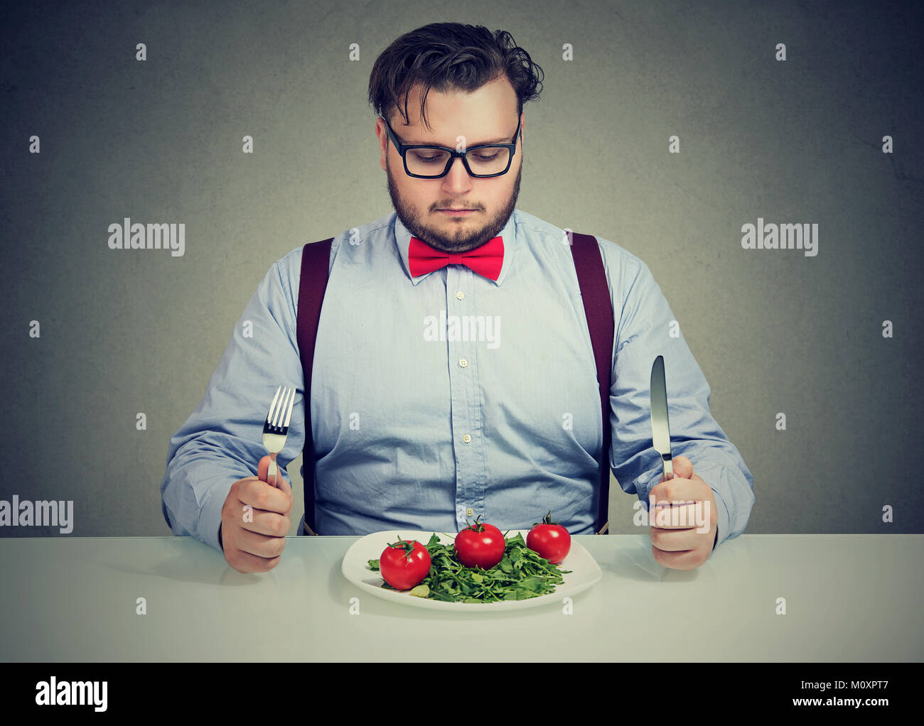Young overweight man concentrated on healthy salad trying to lose weight. - Stock Image