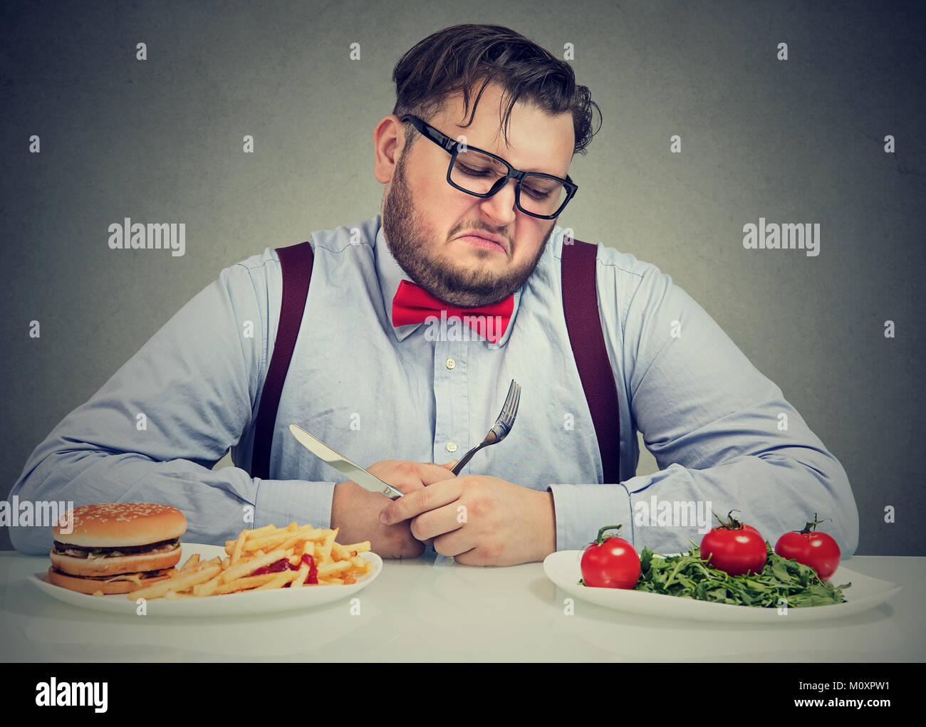 Overweight man in formal outfit looking at salad†with hate while craving juice hamburger. - Stock Image