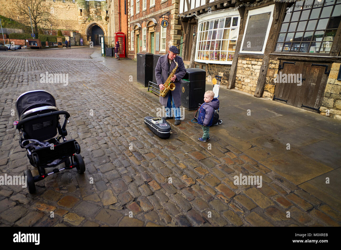 A small puzzled child meets a man playing a saxaphone in the street at Lincoln - Stock Image