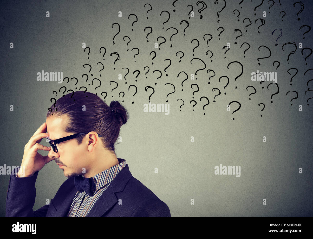 Elegant man in eyeglasses rubbing forehead with question marks on gray backdrop. - Stock Image