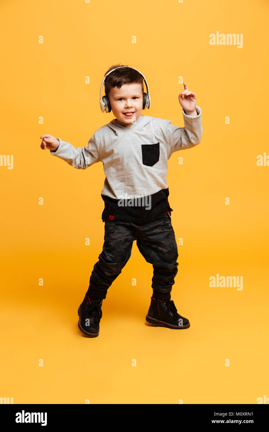 Picture of little funny boy child standing isolated over yellow