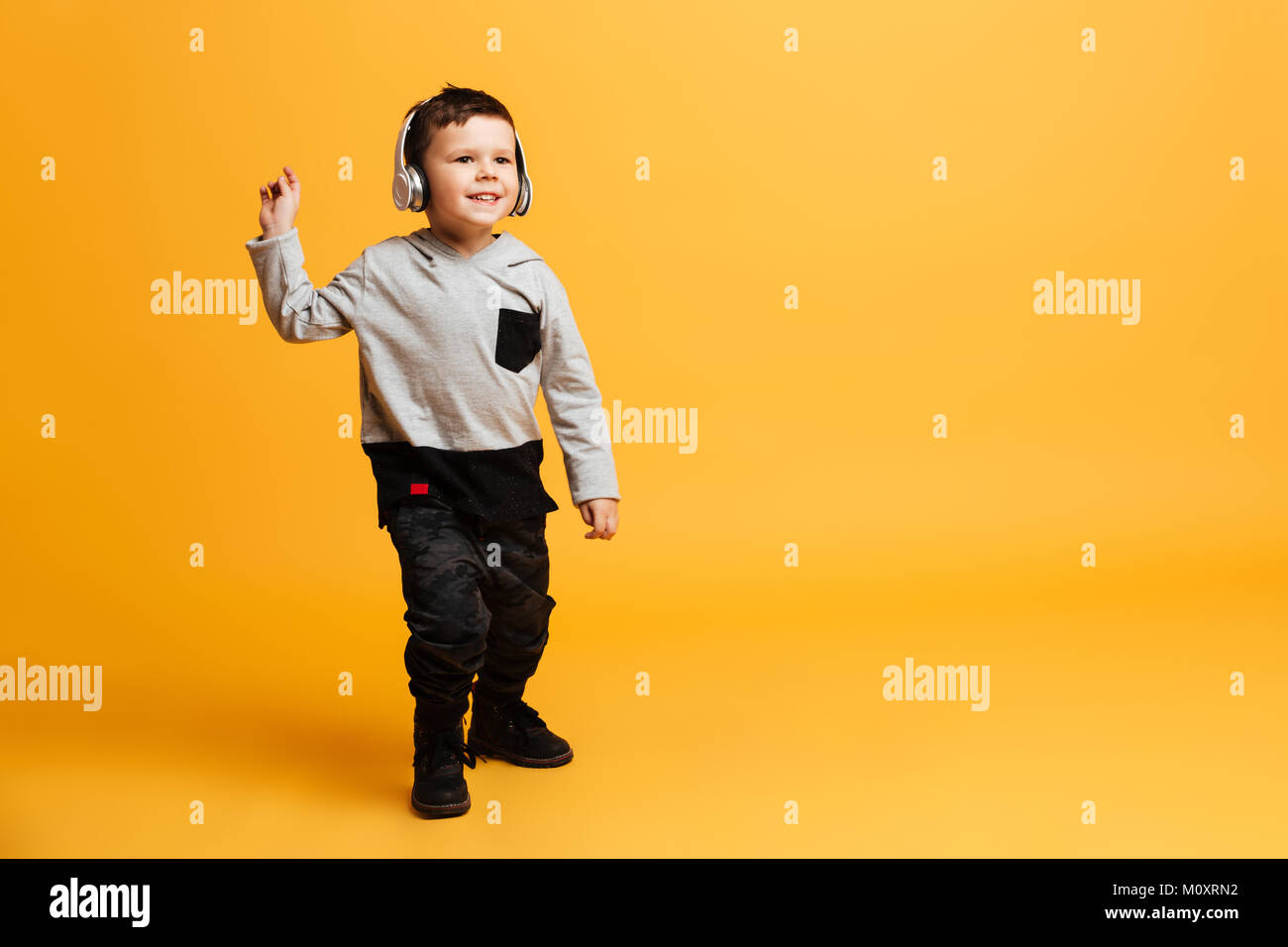 Image of little funny boy child standing isolated over yellow Stock