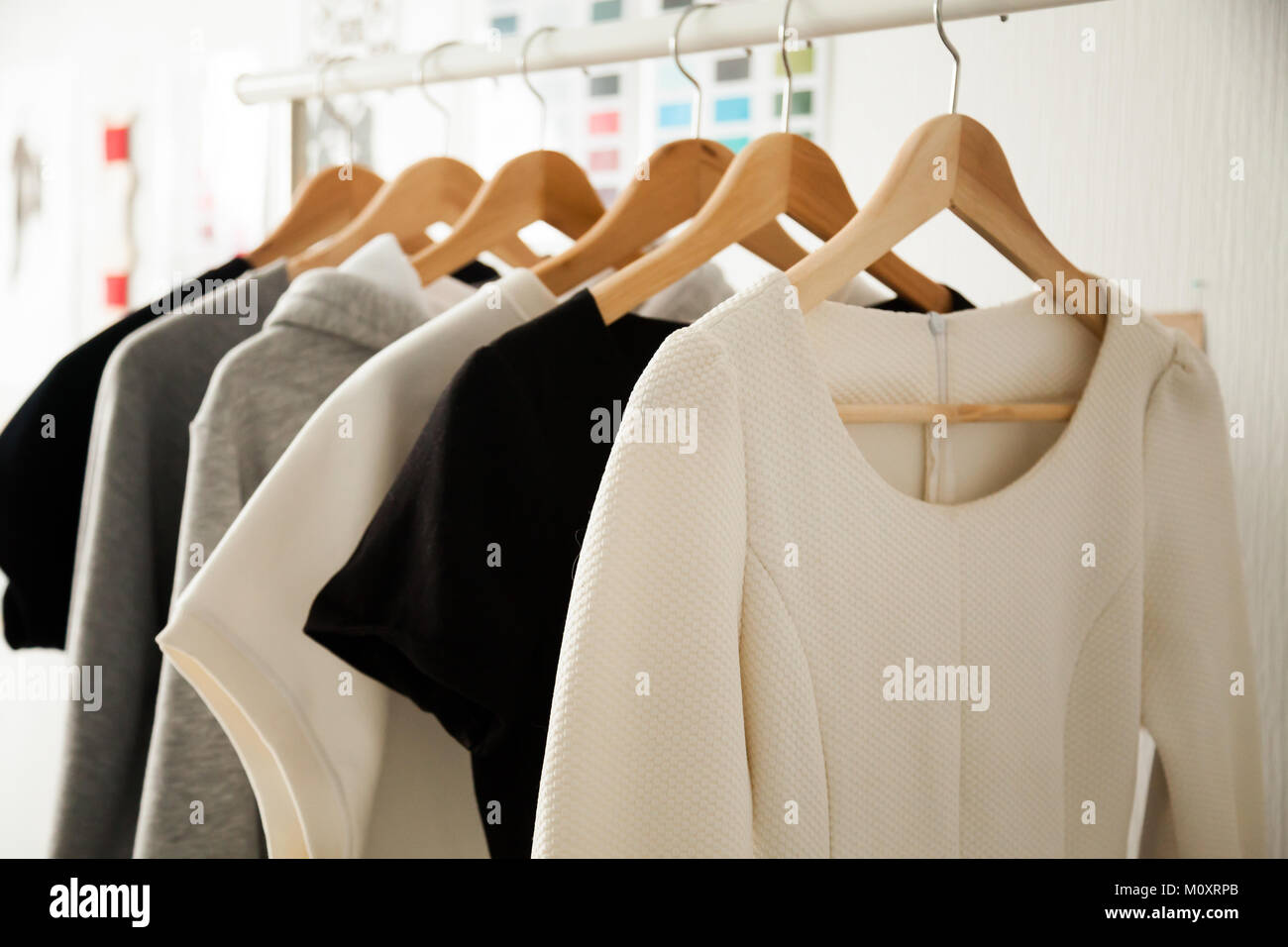 Women clothes hanging on hangers clothing rails, fashion design  - Stock Image