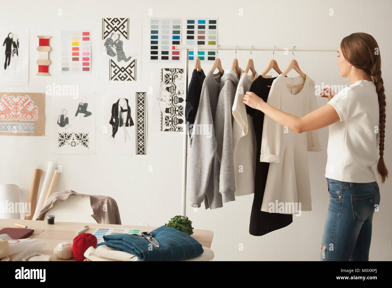 Female fashion designer working on new womenswear collection in  - Stock Image