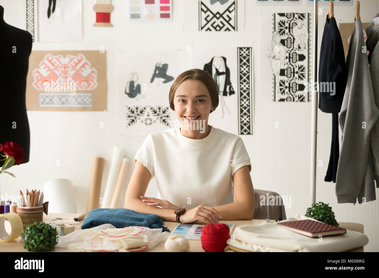 Smiling attractive fashion designer sitting at workplace looking - Stock Image