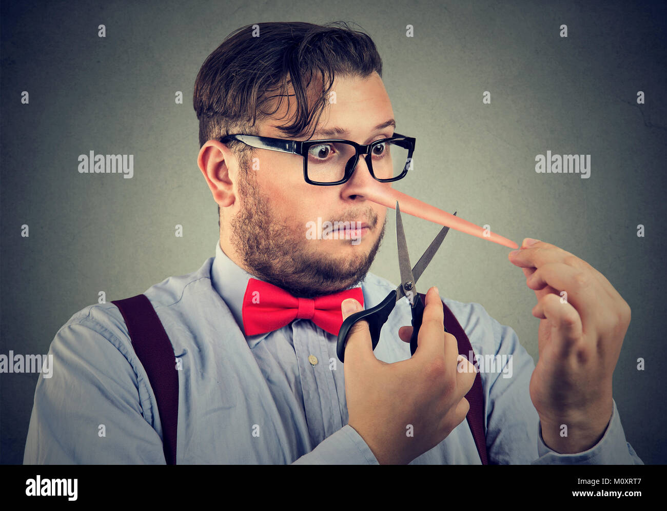Chubby man having long nose of liar trying to cut it off and change situation. - Stock Image