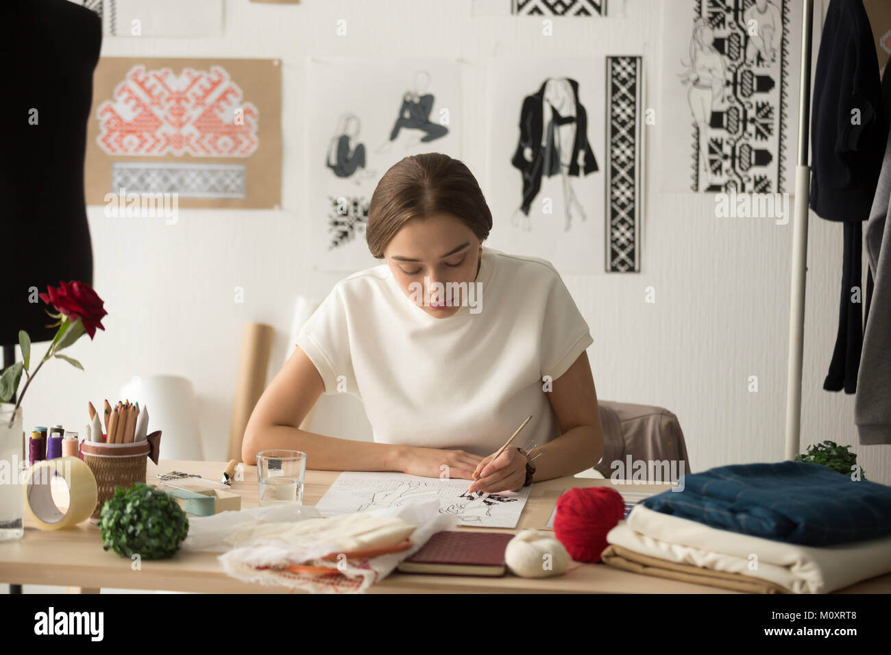 Inspired fashion designer working in studio drawing new collecti - Stock Image