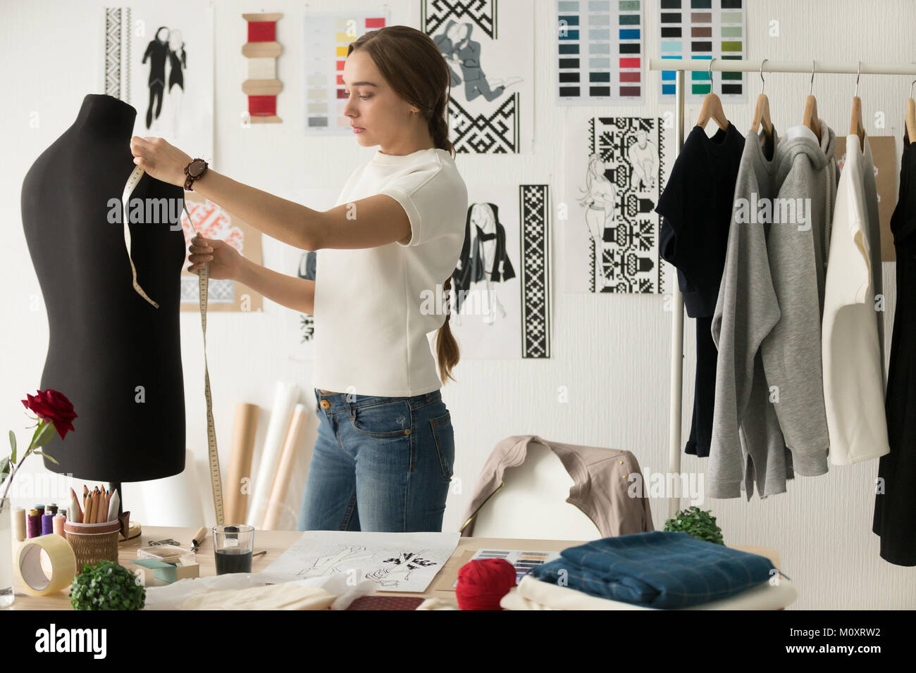 Woman fashion designer measuring mannequin in cozy creative desi - Stock Image