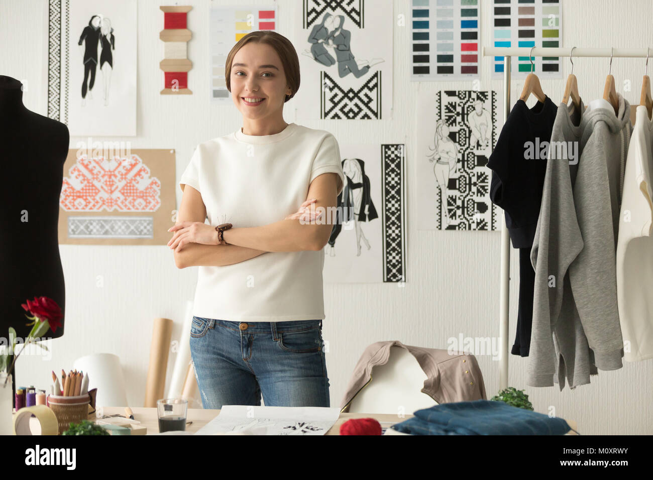 Ethnic embroidered clothing fashion designer standing looking at - Stock Image