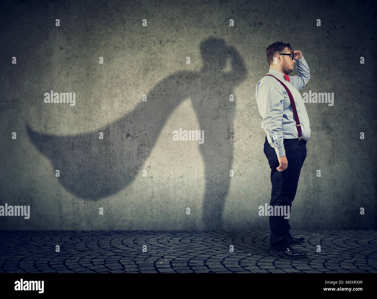 Side view of a chubby man imagining to be super hero looking aspired. - Stock Image