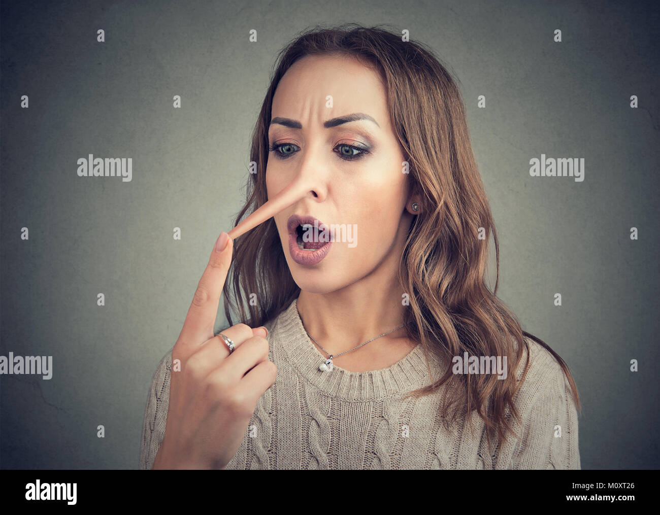 Young casual woman touching extended nose of liar looking shocked. - Stock Image
