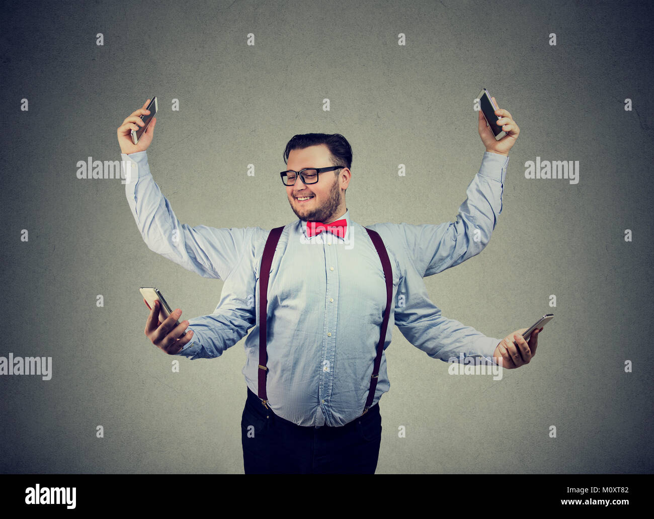 Chunky young man in formal clothing having four arms and using smartphones being multitasking. - Stock Image