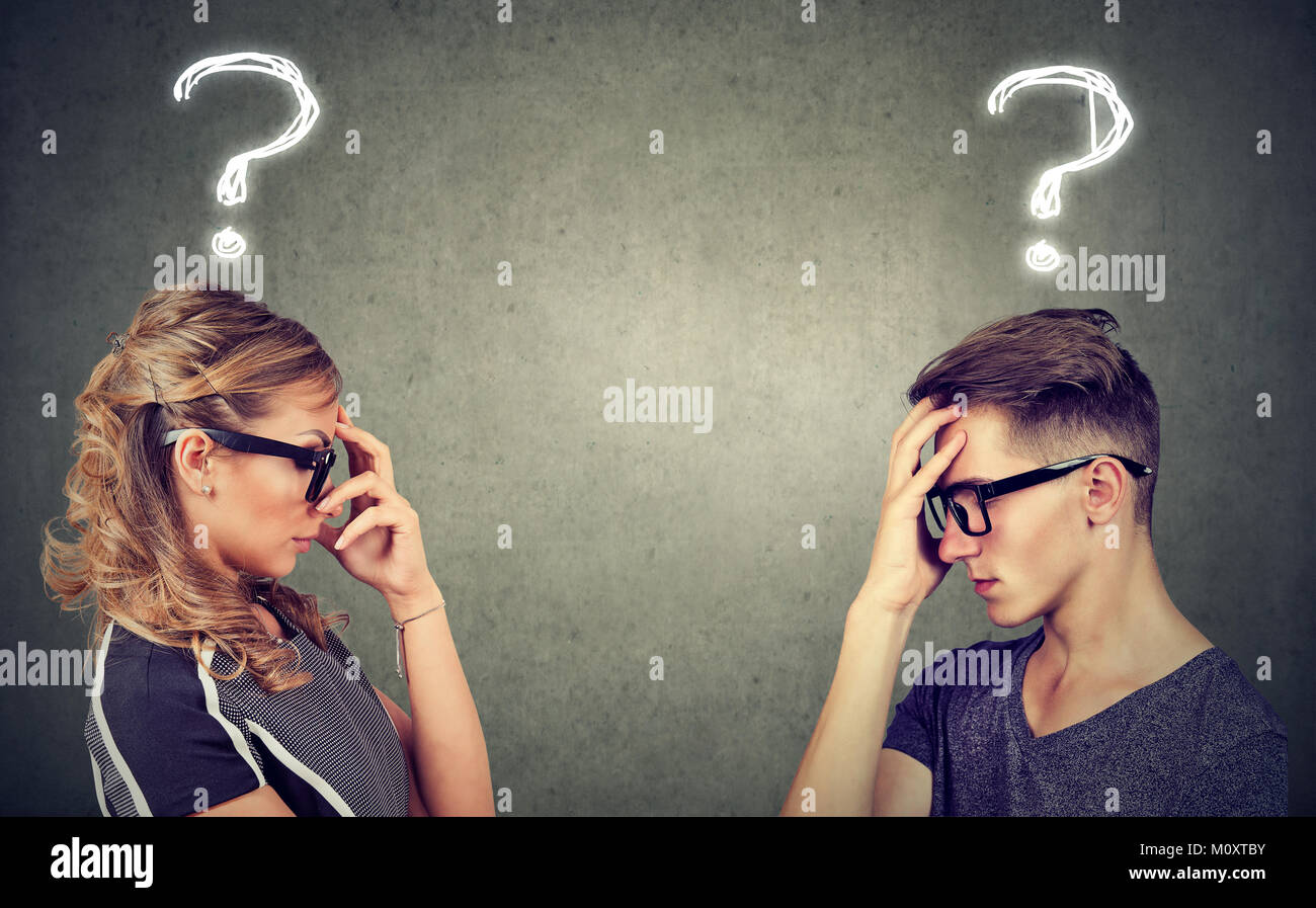 Side view of anxious man and woman having difficulties in marriage looking perplexed. - Stock Image