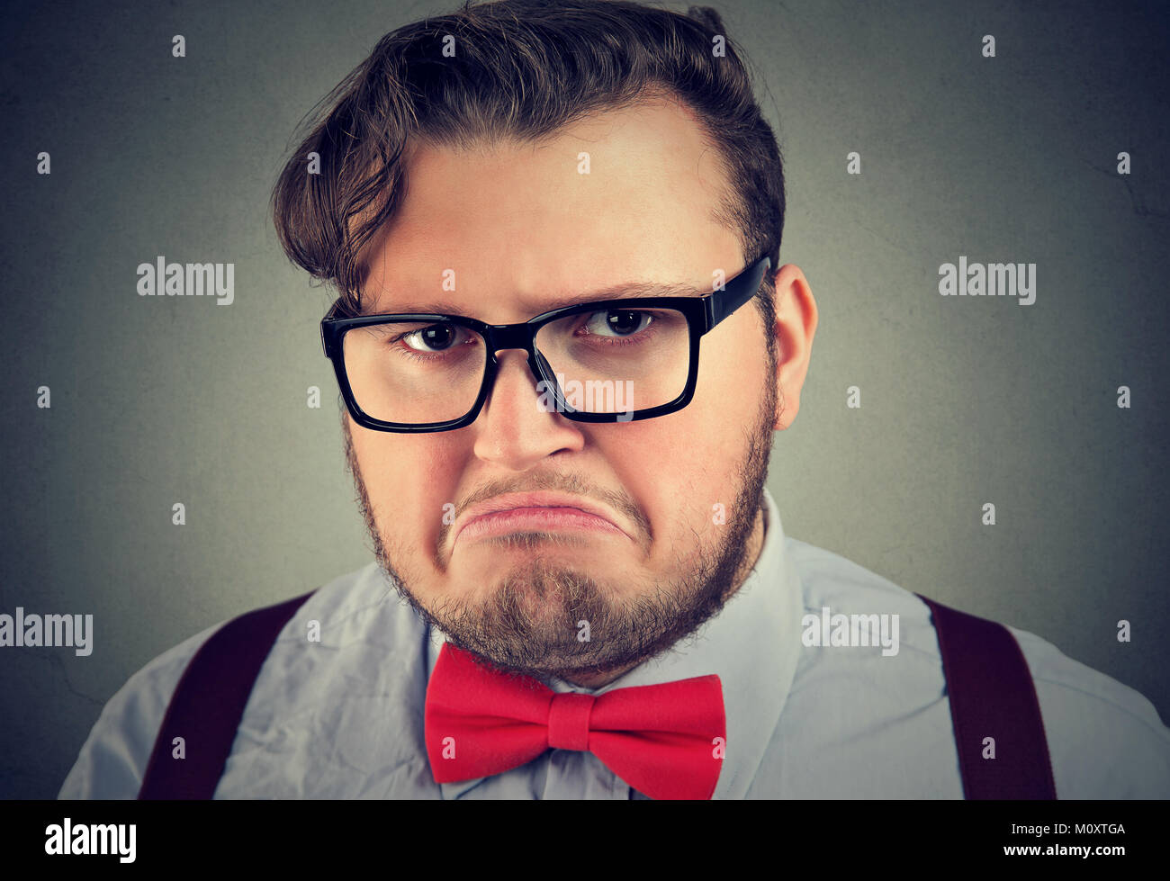 Portrait of chunky man in eyeglasses looking offended and gloomy posing at camera. - Stock Image