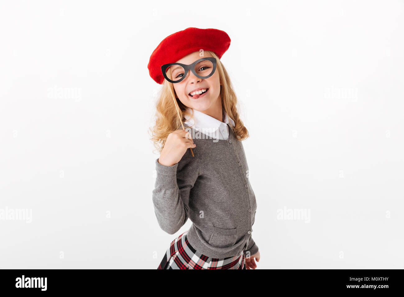 Portrait of a smiling little schoolgirl dressed in uniform grimacing and looking at camera isolated over white background - Stock Image