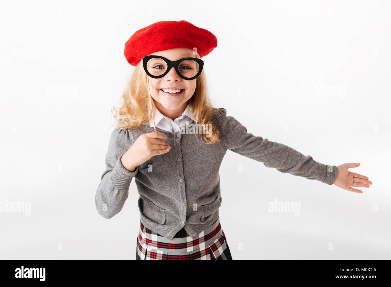 Portrait of a cheerful little schoolgirl dressed in uniform grimacing and looking at camera isolated over white - Stock Image