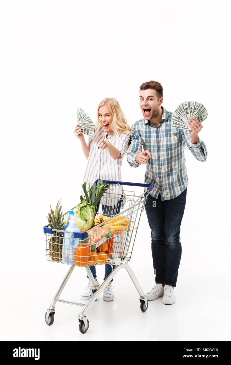 Full length portrait of a joyful couple holding bunch of money banknotes and pointing fingers at camera while standing - Stock Image