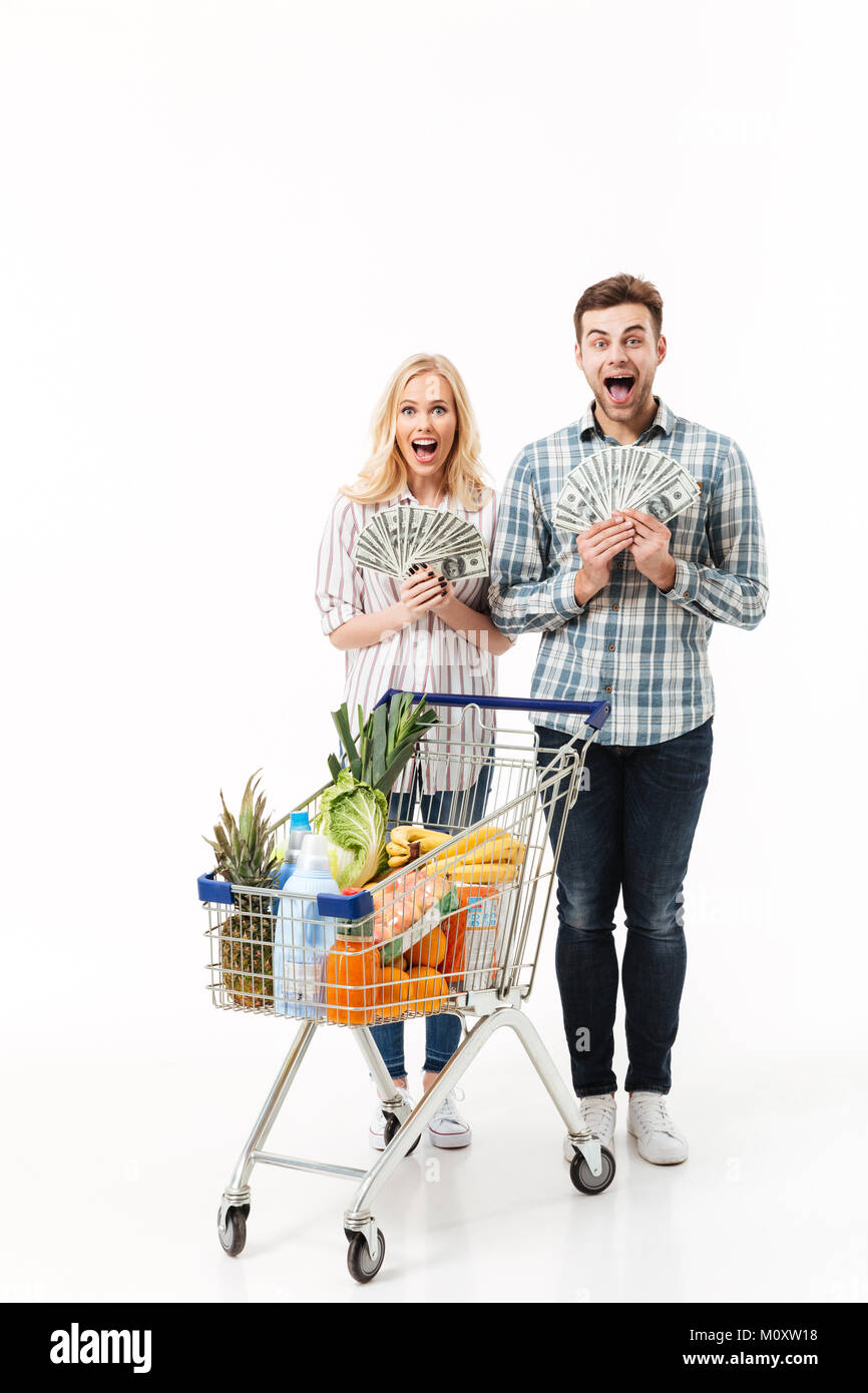 Full length portrait of a surprised couple holding bunch of money banknotes and looking at camera while standing - Stock Image