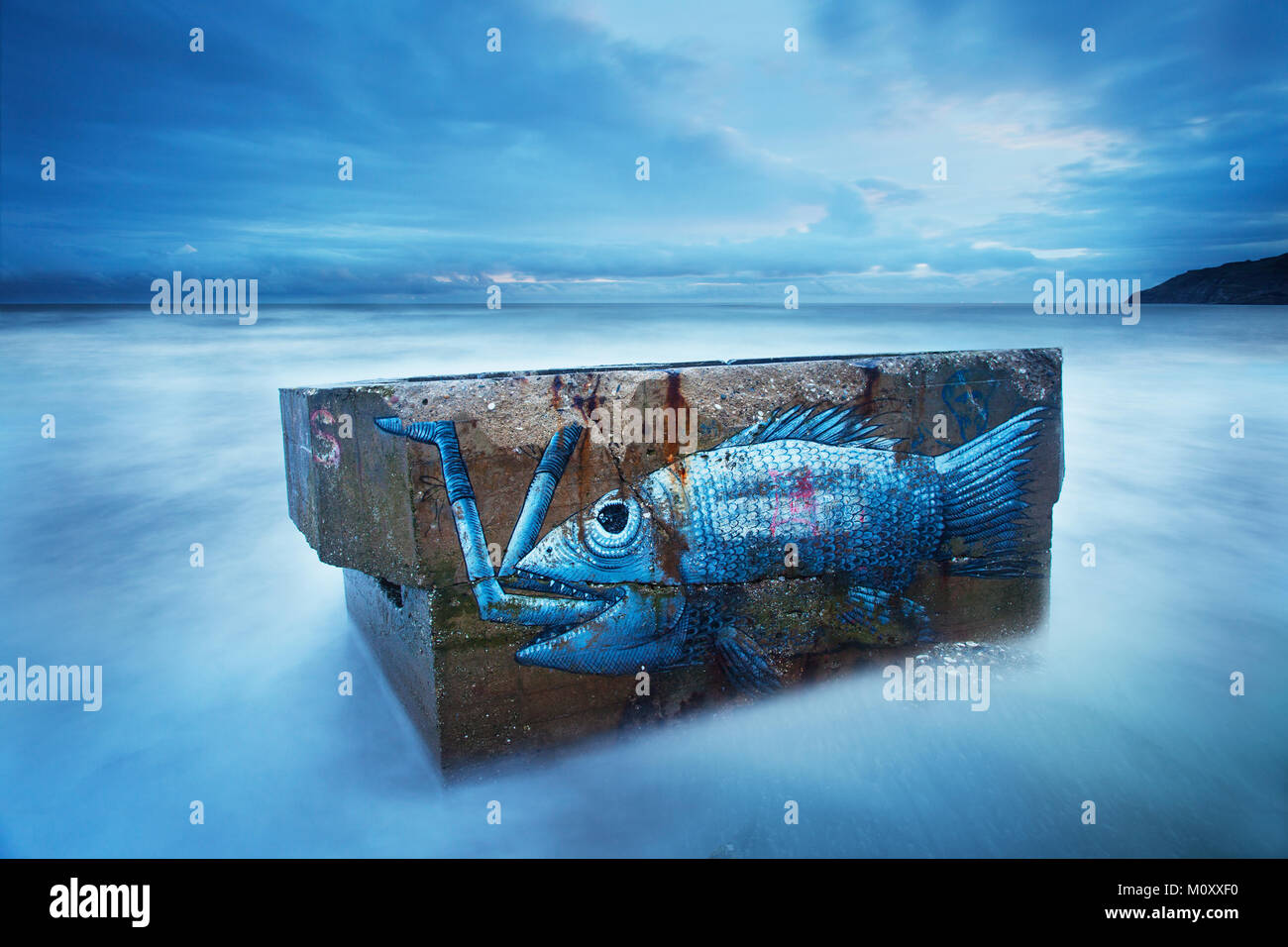 A Graffiti fish on a pill box on Cayton Bay at high tide with the sea lapping the pill box. Long exposure. - Stock Image
