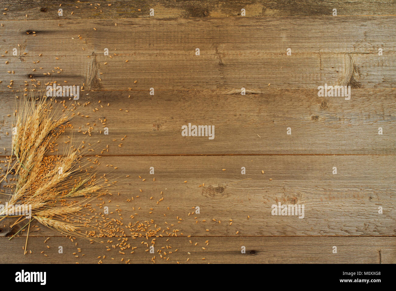 frame of wheat ears with grains on the wooden background - Stock Image