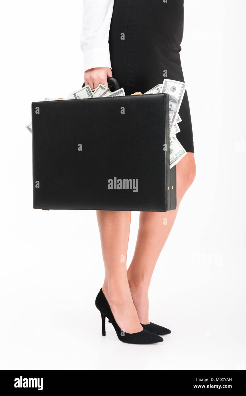 Close up portrait of a businesswoman wearing high heels holding briefcase full of money banknotes isolated over - Stock Image