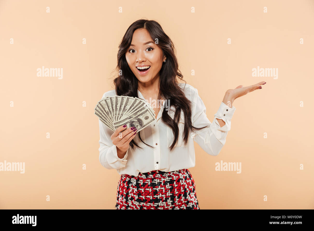 Excited young lady with long dark hair holding fan of 100 dollar bills expressing gladness, having a lot of money - Stock Image