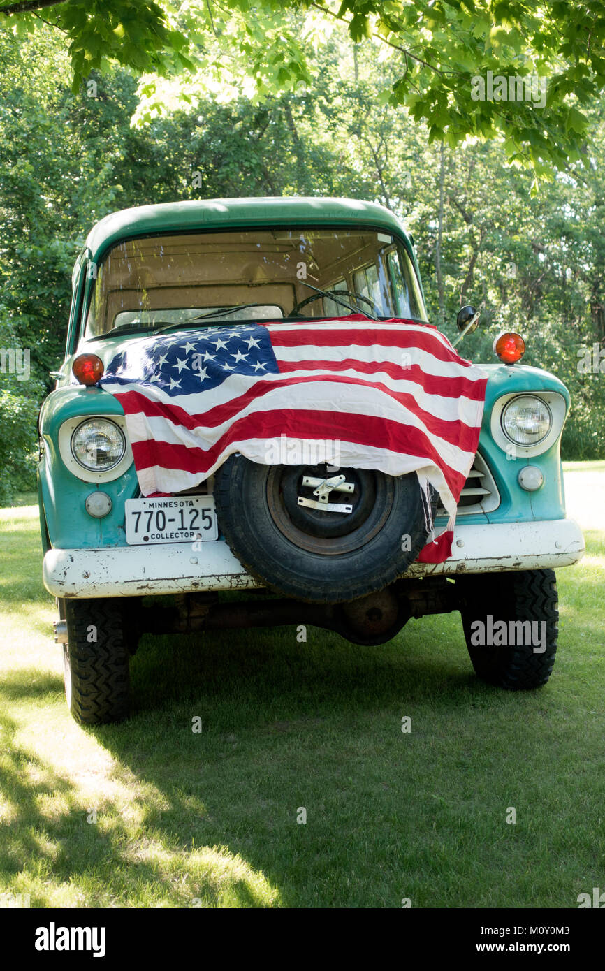 American flag draped Chevrolet 1956 Carryall Suburban truck celebrating Independence Day on the Fourth of July . - Stock Image