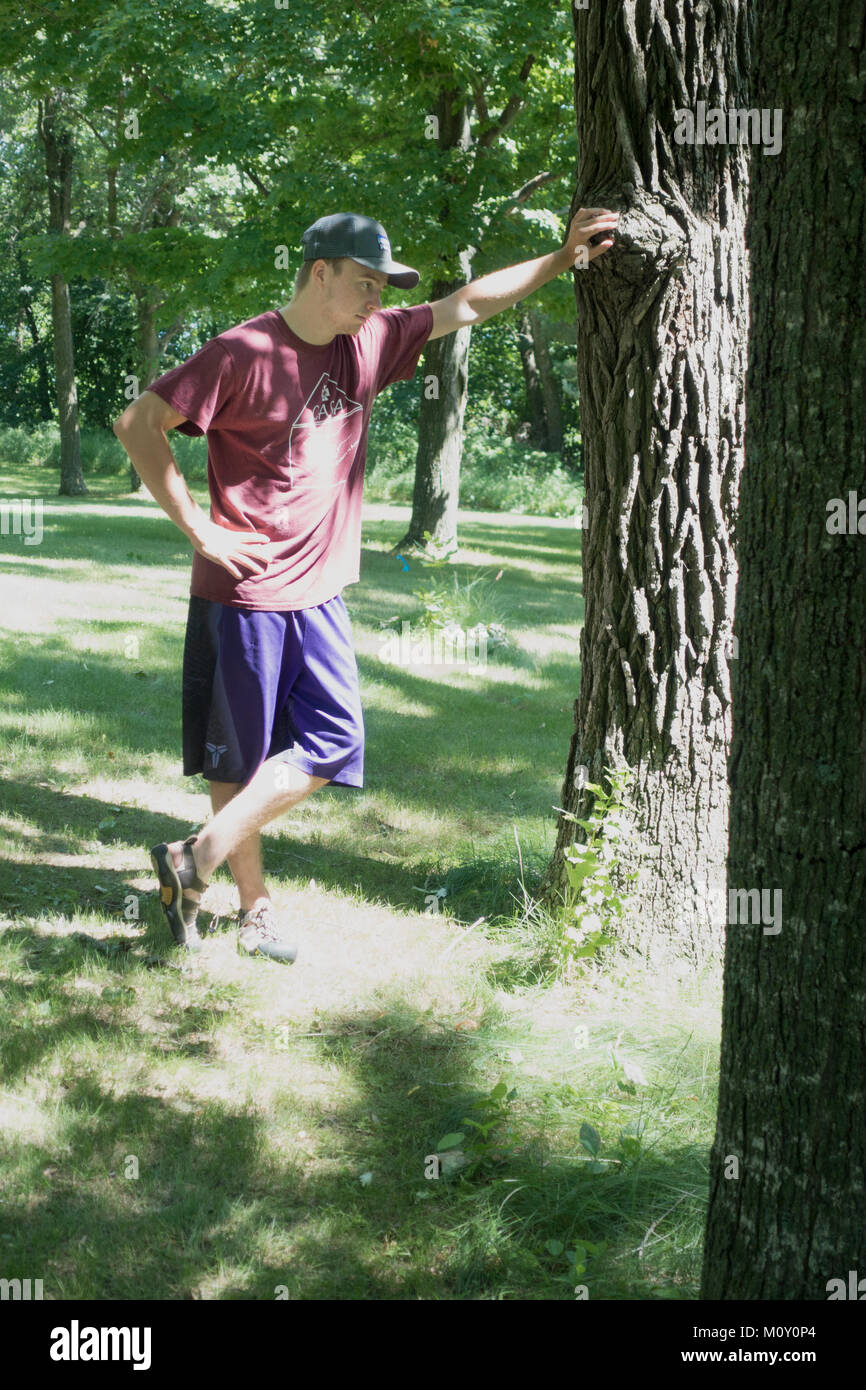 Teenage boy leaning against a tree contemplating his future. Clitherall Minnesota MN USA - Stock Image