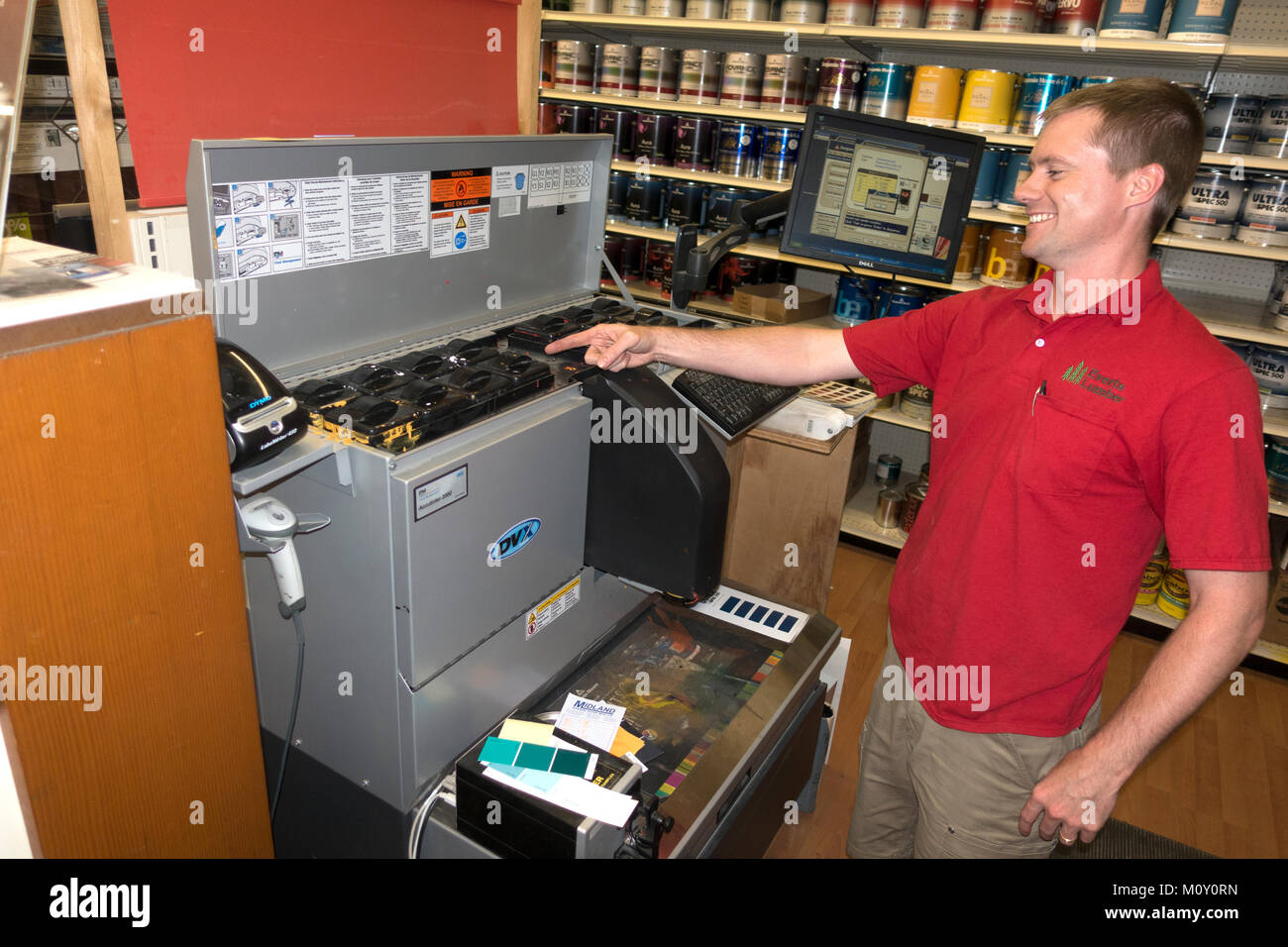 Oops, good-natured electronic paint mixing employee pointing out where the yellow tinted paint has overflowed its - Stock Image