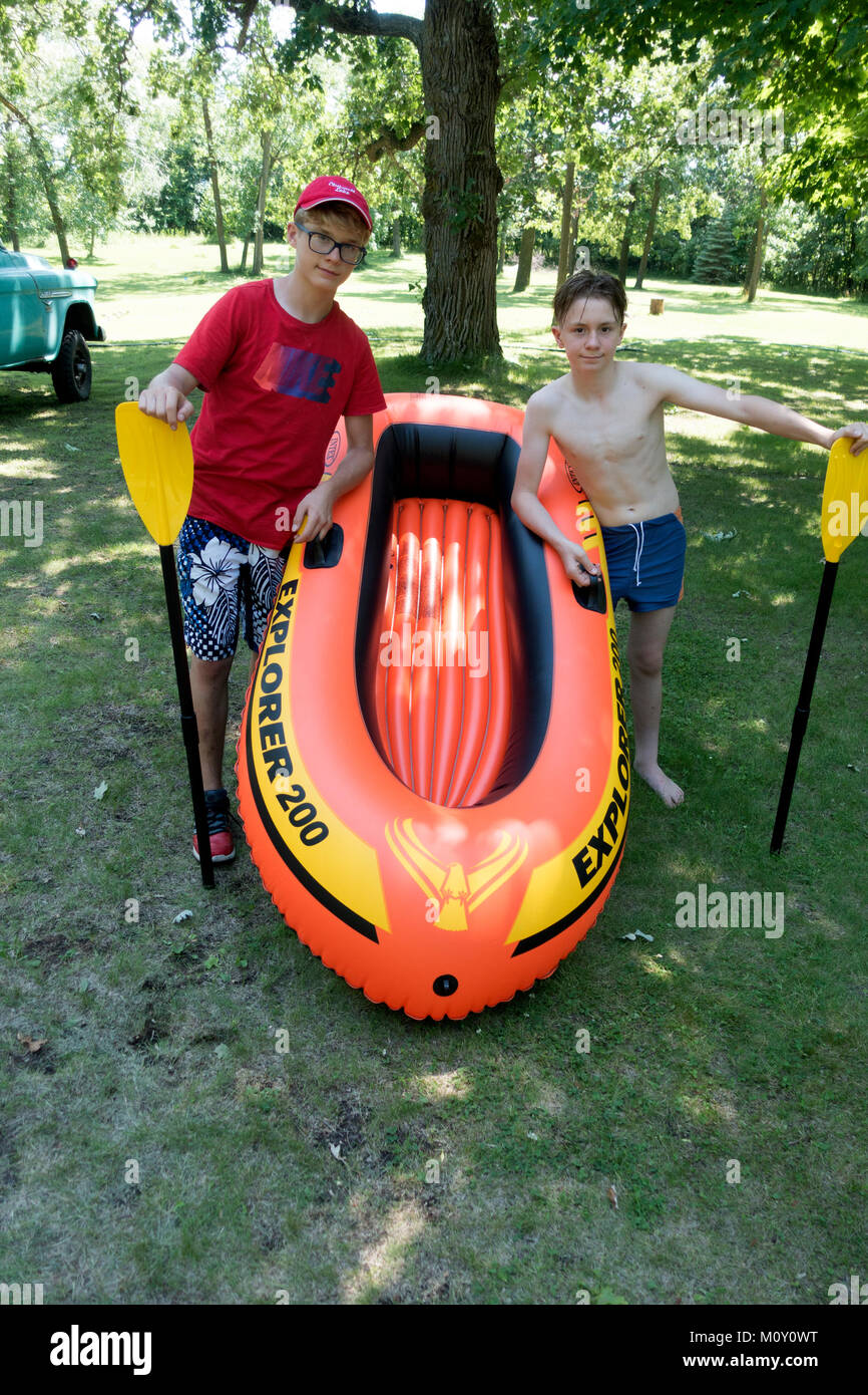 My two grandsons holding paddles ready to launch their new 'Intex Explorer 200' raft. Clitherall Minnesota - Stock Image