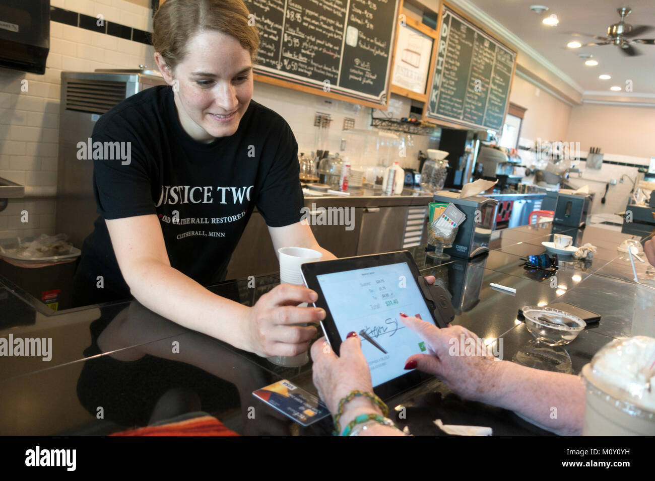 Waitress at the restored 'Justice Two Coffeehouse and Eatery' malt shop helping customer pay her bill electronically. - Stock Image
