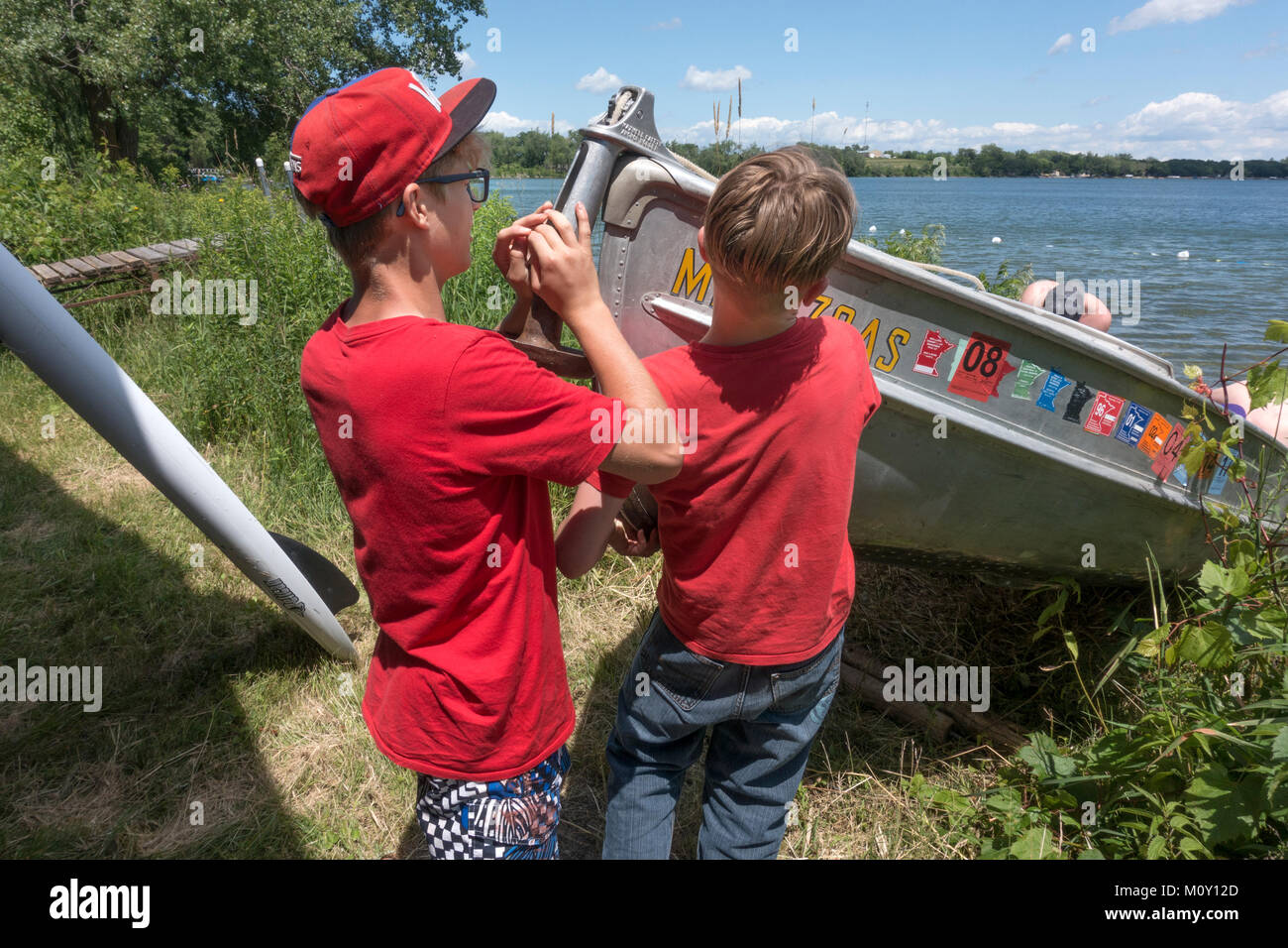 Brothers pulling their end of the aluminum fishing boat out of the water through uncut pollinator weeds from Lake - Stock Image
