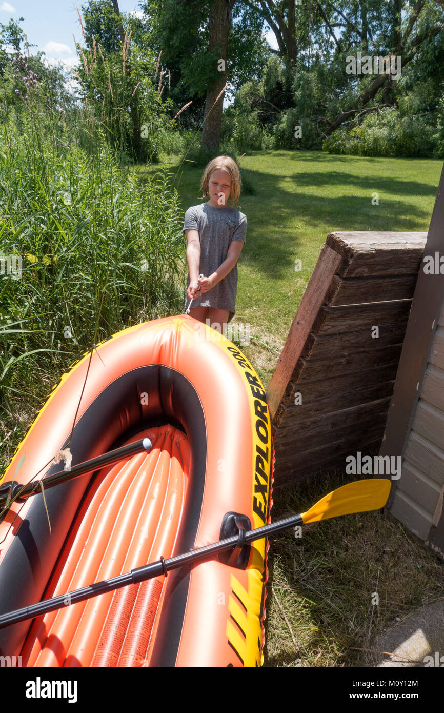 Girl age 10 does her share by pulling inflatable raft through uncut pollinator weeds from Lake Clitherall Minnesota - Stock Image