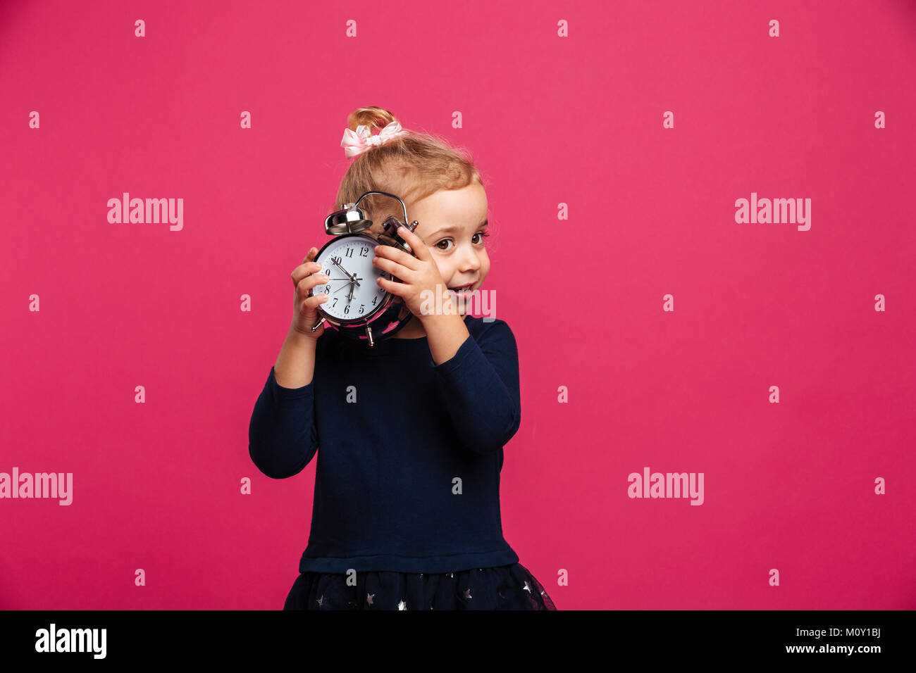 Intrigued young blonde girl holding alarm clock in studio over pink background - Stock Image