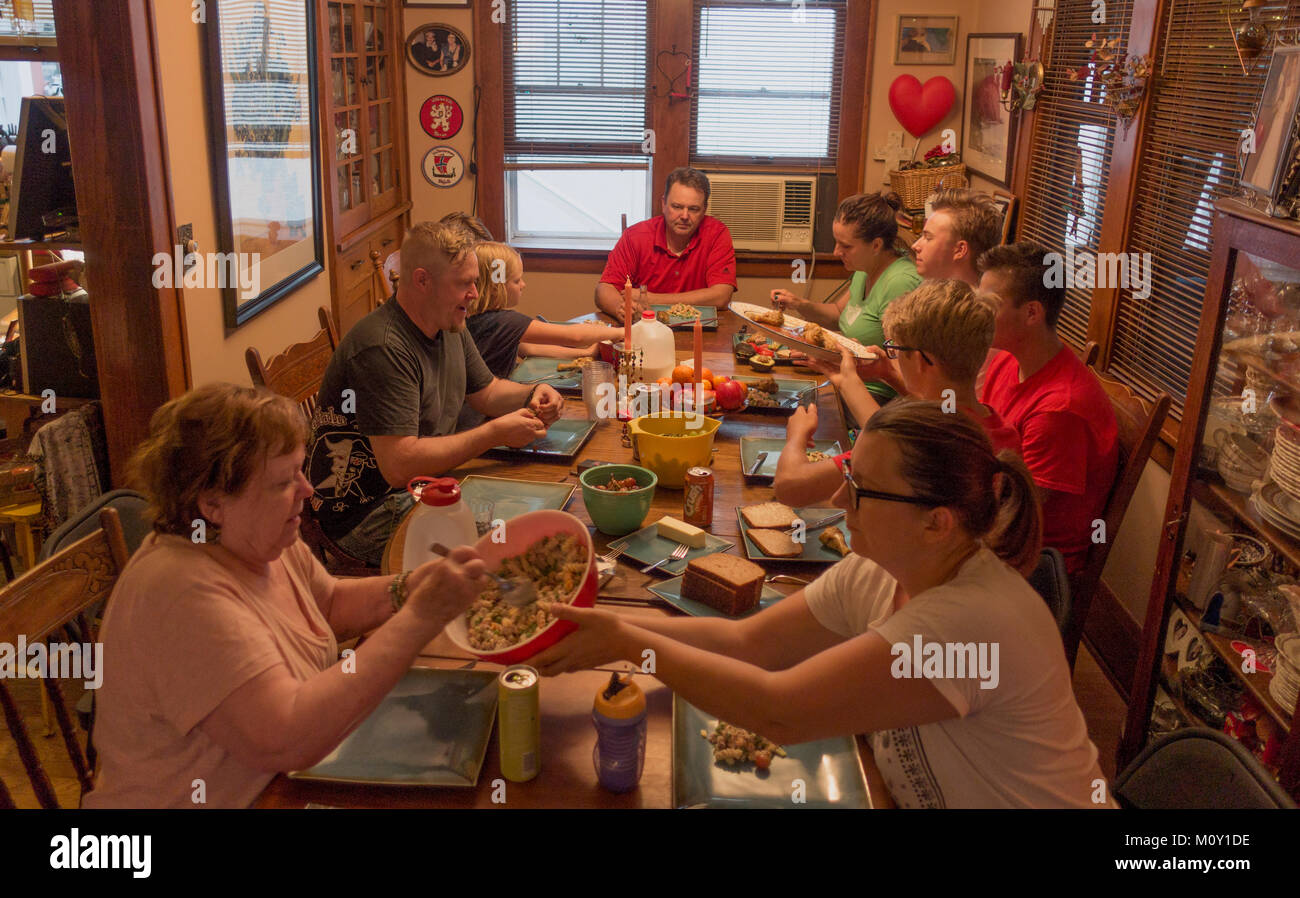 Extended family of three generations having dinner together at a long table. St Paul Minnesota MN USA - Stock Image