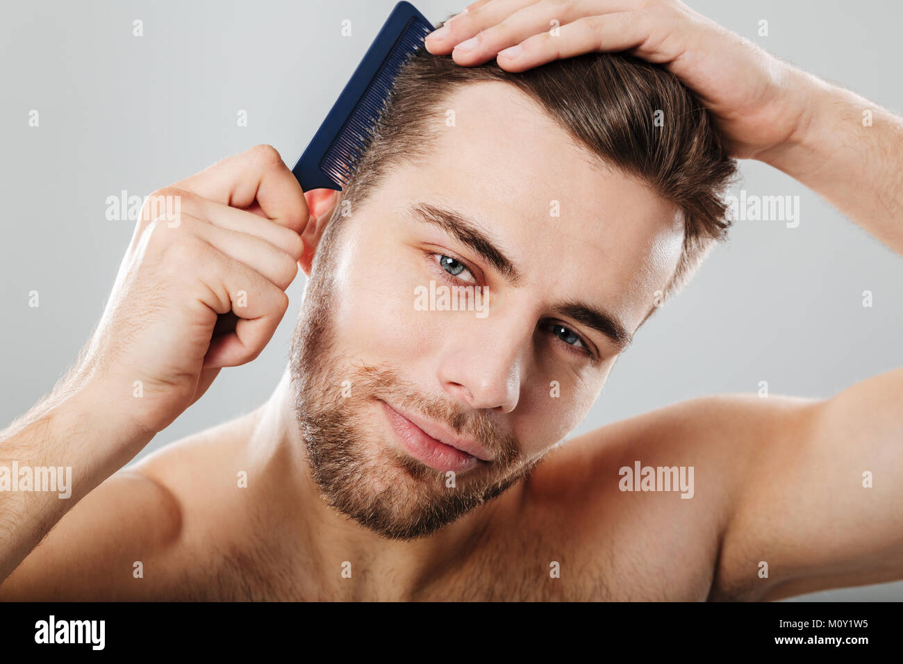 Close up portrait of a smiling man combing his hair isolated over gray background Stock Photo