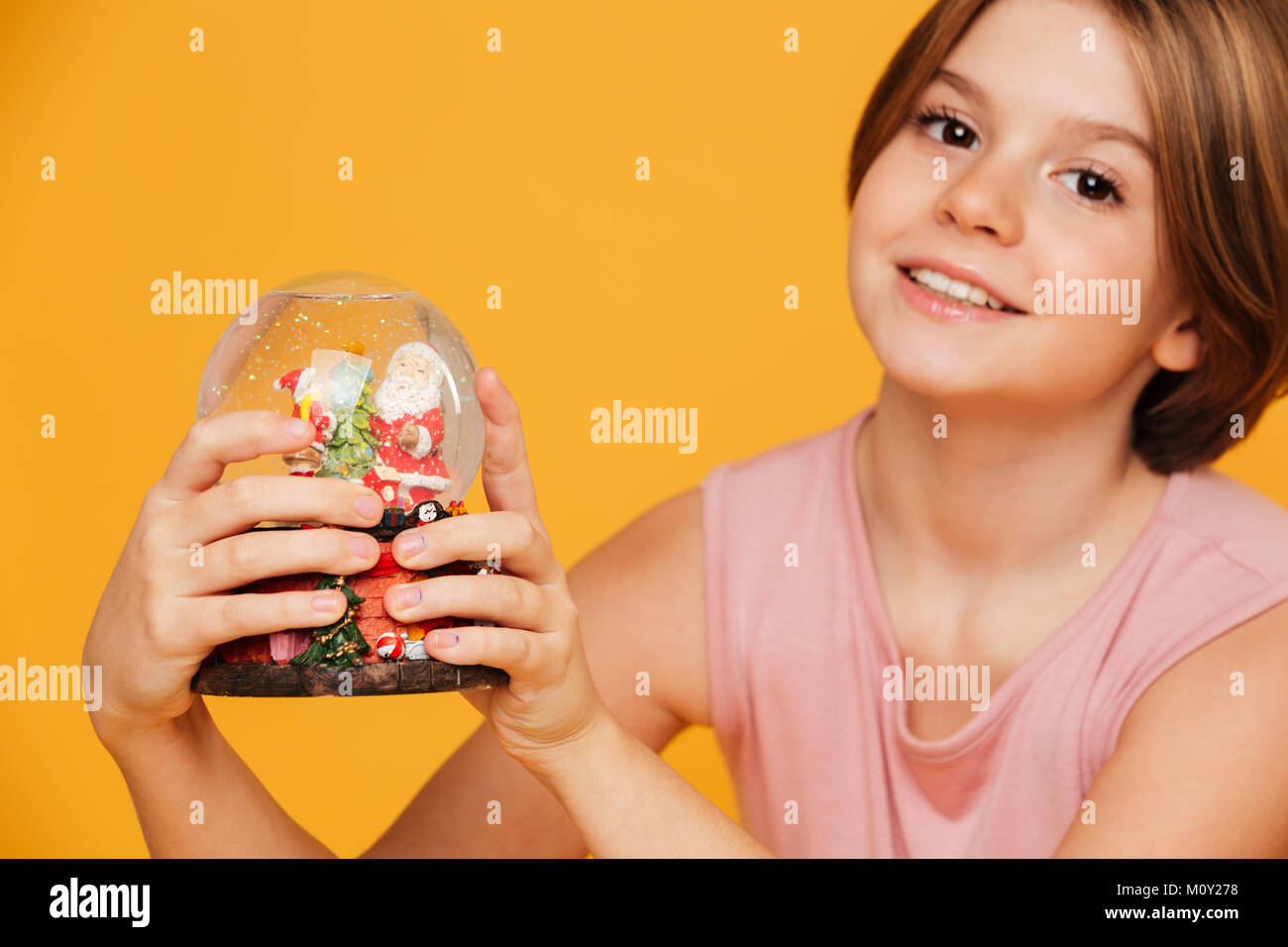Portrait of beautiful smiling girl in pink dress looking camera and holding snow globe in hands isolated over yellow Stock Photo