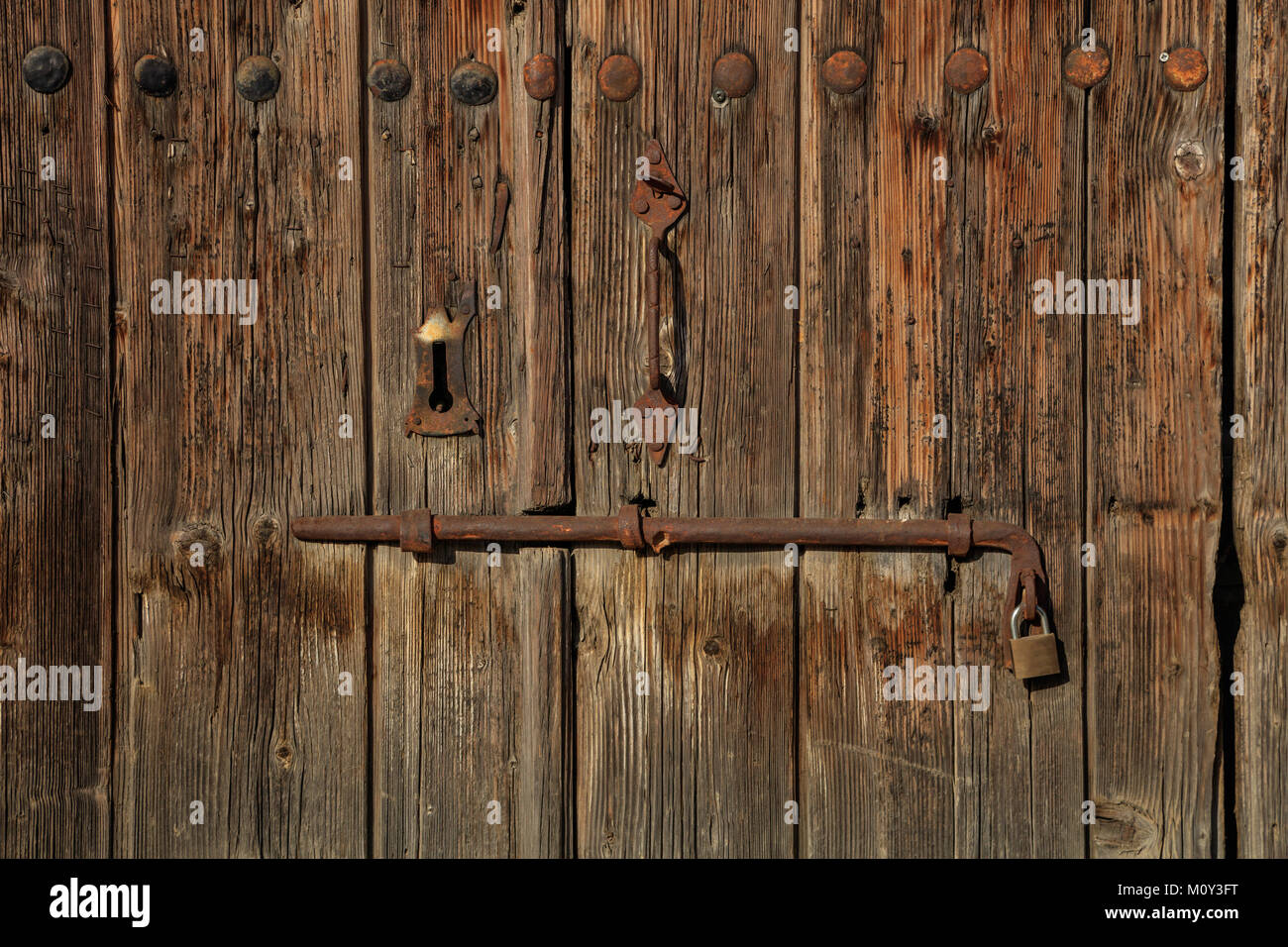 Wooden brown door. Timeworn blank, banner, background with rusty latch and padlock. Closeup, details - Stock Image