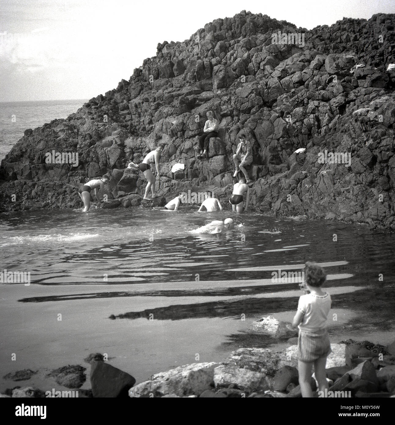 1950s, historical picture showing a group youngsters taking a dip in the sea at a small rocky inlet at Co Antrim - Stock Image