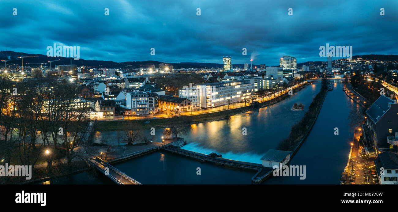 Aerial panoramic view of Zurich skyline at dawn, in the foreground the Limmat river. - Stock Image