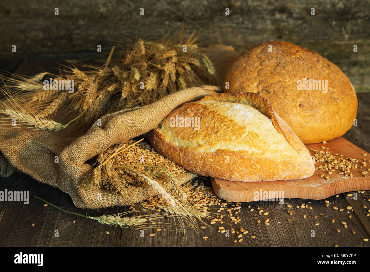 bread, wheat, ears of corn on a wooden background on coarse fabric - Stock Image