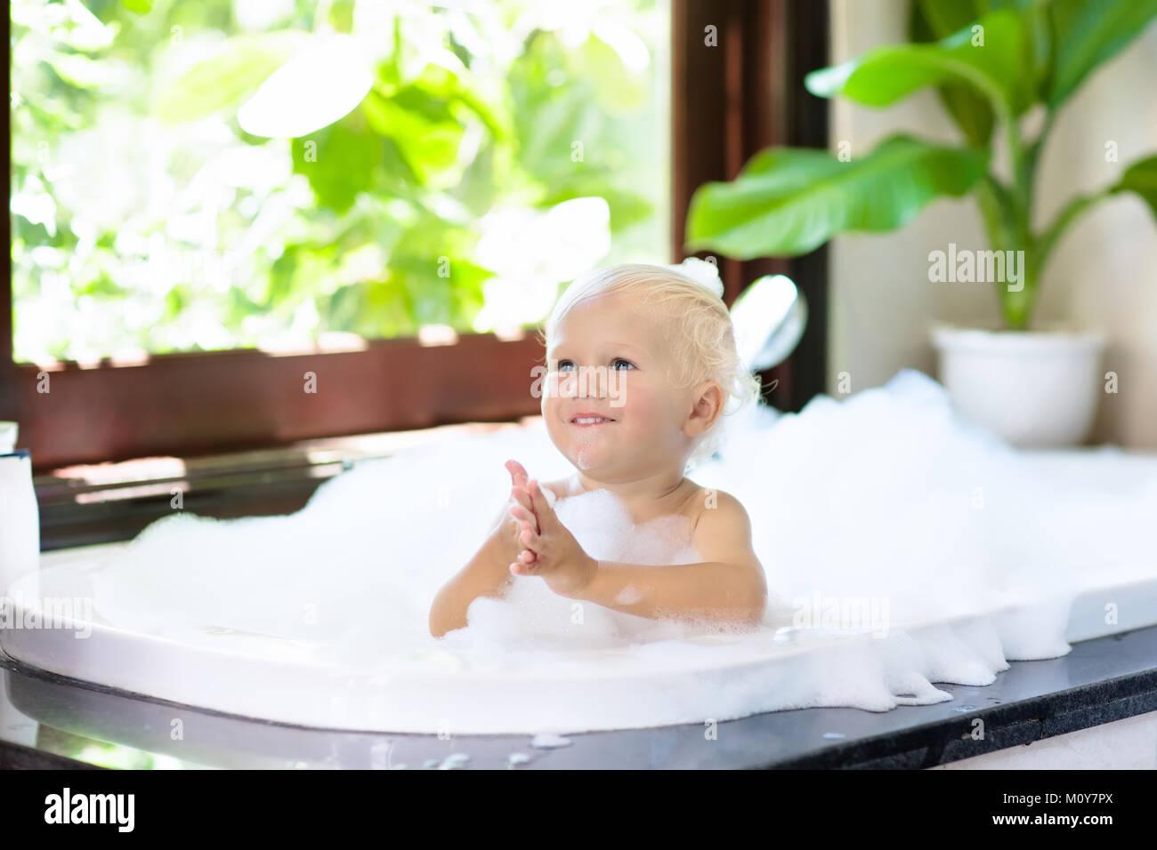 Little child taking bubble bath in beautiful bathroom with big ...